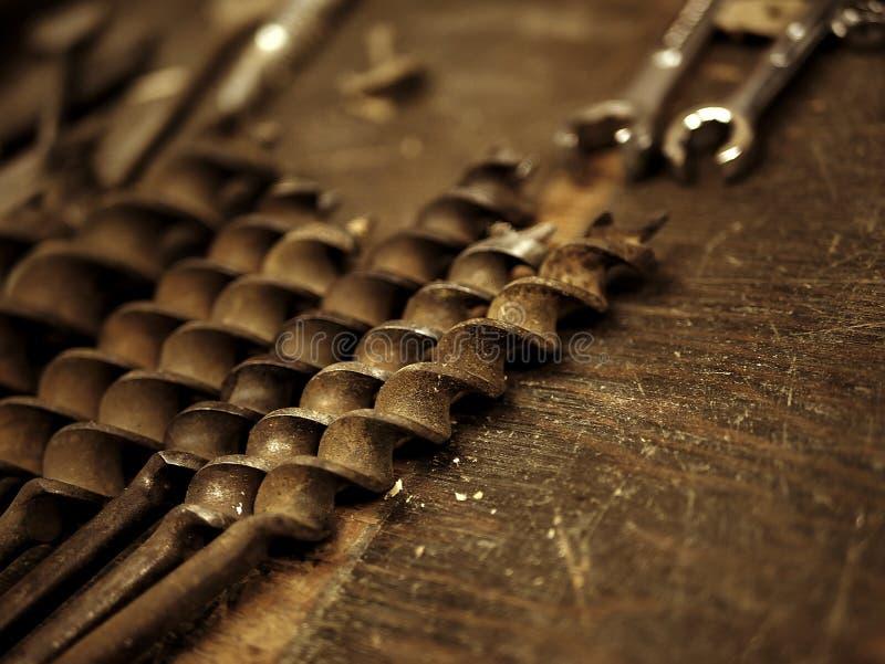 在车库的建筑工具:在木工作台的钻头 库存照片