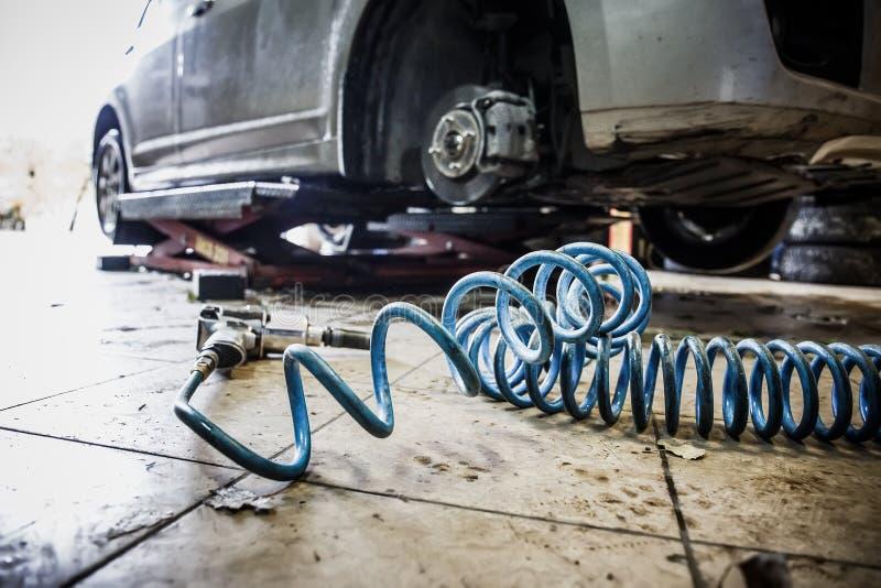 在车库的汽车在汽车机械师有修理设备-气动力学的板钳的特别机器的修理公司车间 免版税库存图片