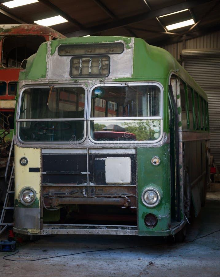 在车库的葡萄酒老减速火箭的绿色公共汽车 库存照片