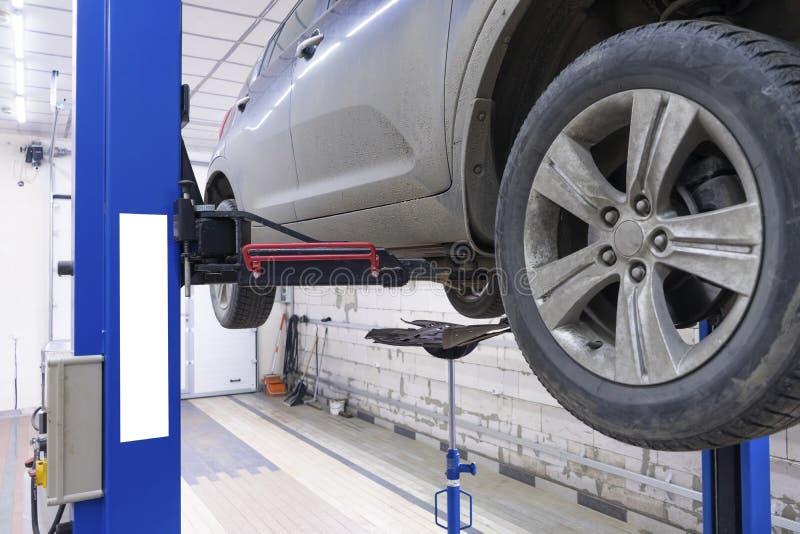 在车库的黑汽车用为修理准备的特别设备 免版税库存图片