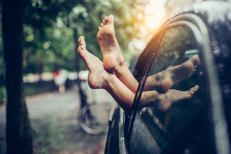 在车窗外面的女性腿棍子 获得乐趣和放松在汽车的妇女在旅行期间 免版税库存图片