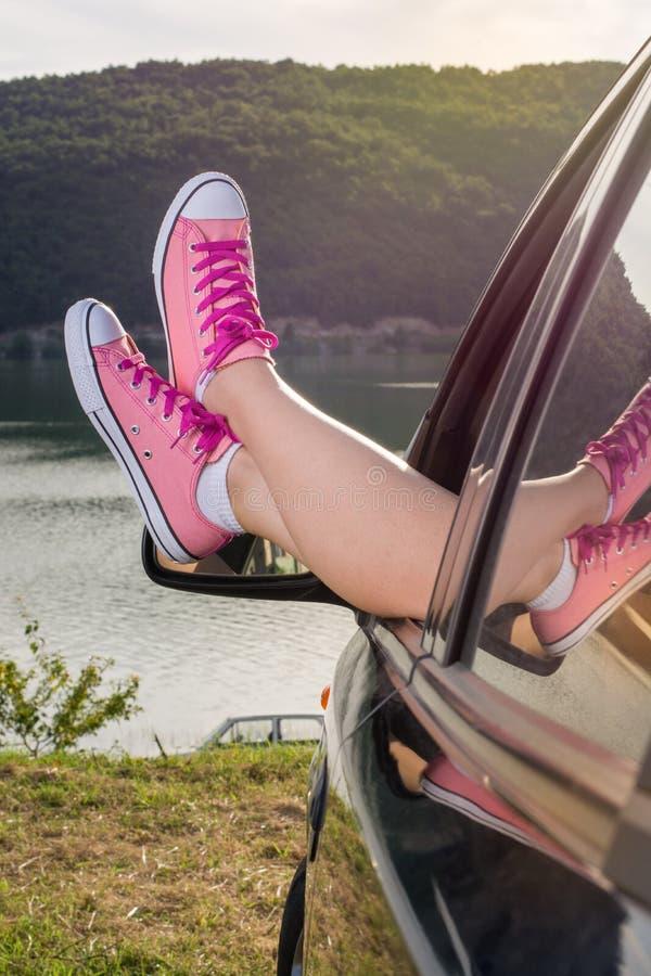在车窗外面的腿由湖 免版税库存图片