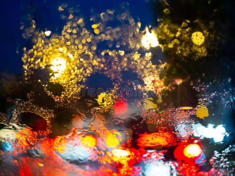 在车窗的被弄脏的雨下落与路在雨季摘要背景的光bokeh 免版税图库摄影