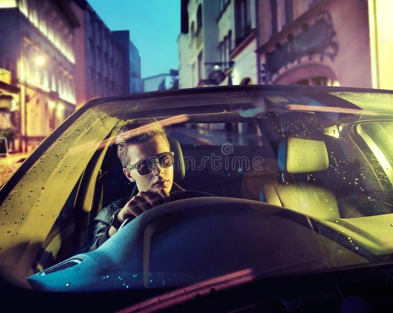 在车轮后的英俊的人 图库摄影