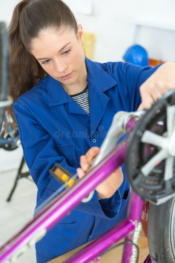 在车间骑自行车修理在自行车的技工轮子 库存图片