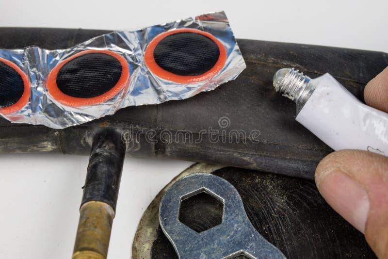 在车间骑自行车管、胶浆和补丁 修理黄鹿 库存图片