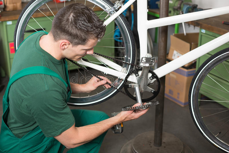 在车间骑自行车修理牙传送带的技工 图库摄影