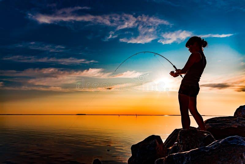 在转动在挪威的钓鱼竿的妇女钓鱼 库存图片