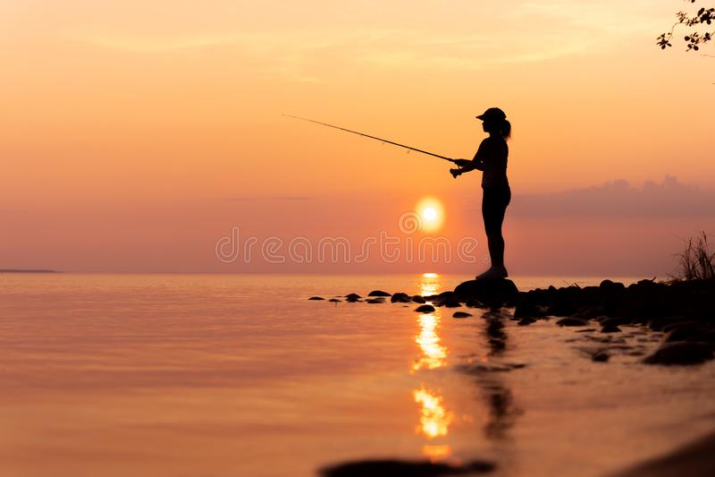 在转动在挪威的钓鱼竿的妇女钓鱼 免版税库存照片