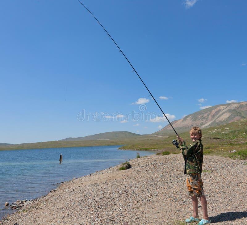 在转动的男孩渔 免版税库存图片