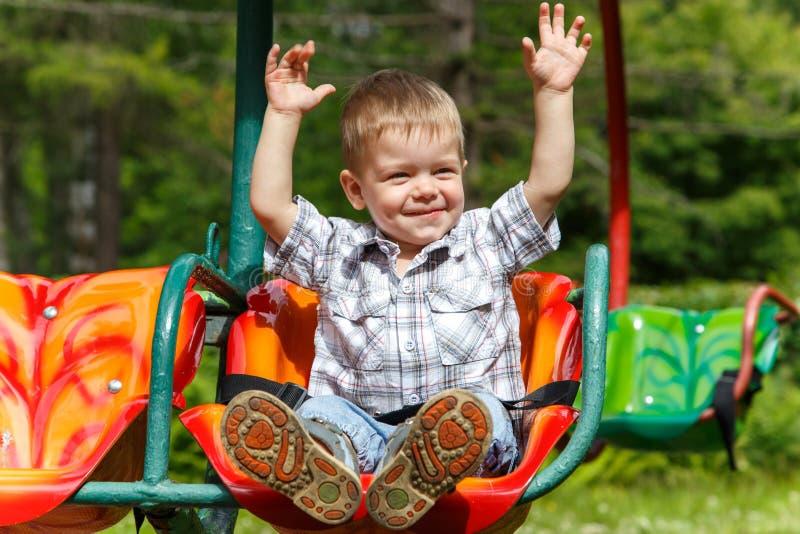 在转盘的无所畏惧的两年老男孩骑马 免版税库存图片