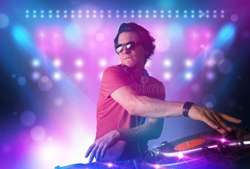 在转盘的音乐节目主持人混合的音乐在与光的阶段和 免版税库存图片