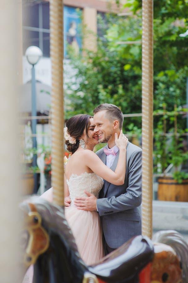 在转盘附近的愉快的新婚佳偶亲吻 免版税图库摄影