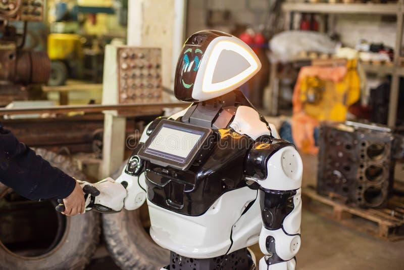在轮子的有人的特点的机器人有在他的胸口的一台显示器的,与一个人握手 老凌乱的车库 免版税库存图片
