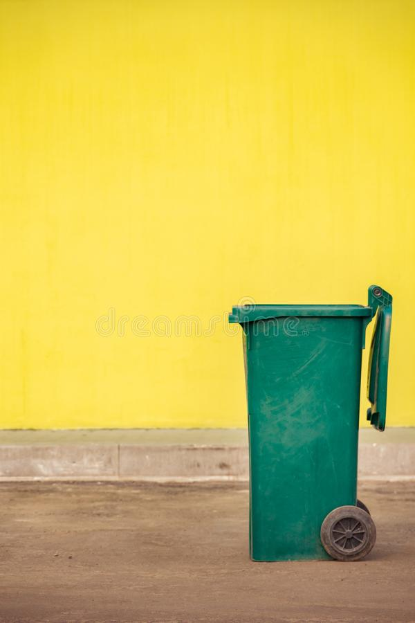 在轮子的绿色塑料垃圾容器在y的背景 免版税图库摄影