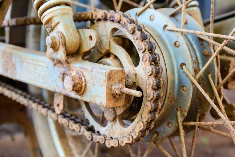 在轮子的老肮脏的摩托车链子有生锈的金属零件的 免版税库存照片