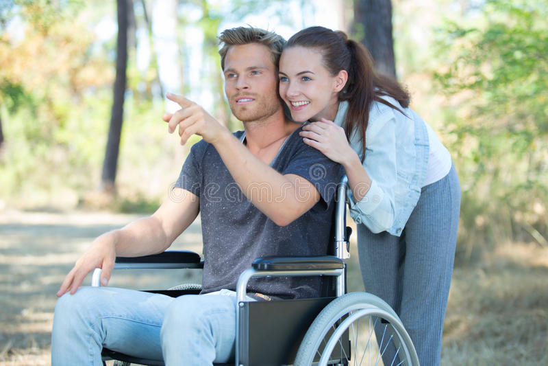 在轮椅步行的夫妇通过森林 免版税库存照片