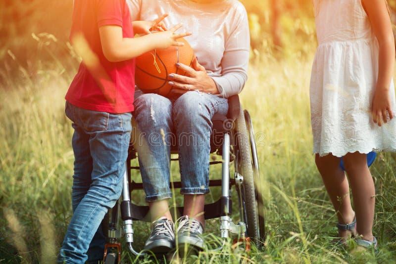 在轮椅的年轻女人的腿有儿童aroud的她 免版税库存图片