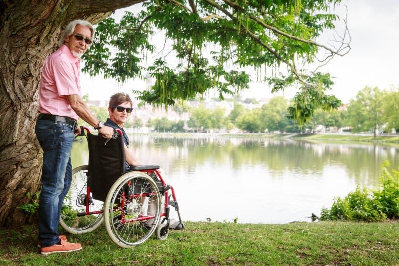 在轮椅的资深夫妇 库存图片