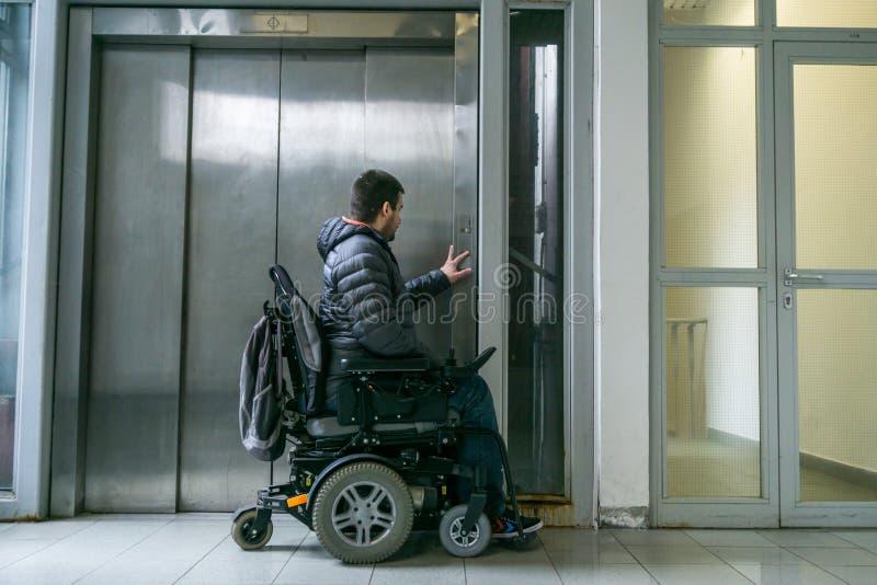 在轮椅等待的电梯的有残障的男性 免版税图库摄影