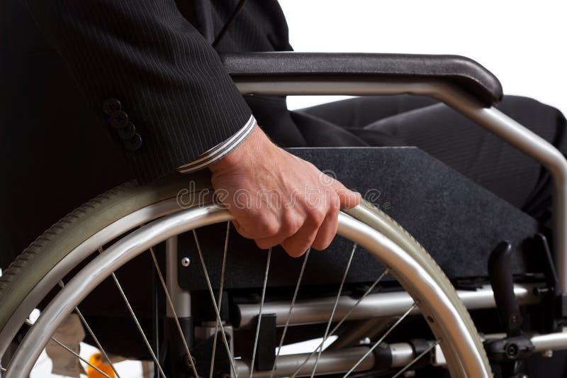 在轮椅轮子的男性手  免版税图库摄影