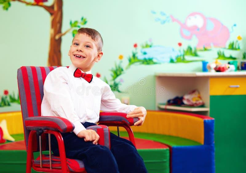 在轮椅,佩带的高兴的旧布的逗人喜爱的愉快的孩子在孩子中心有特别需要的 免版税库存图片