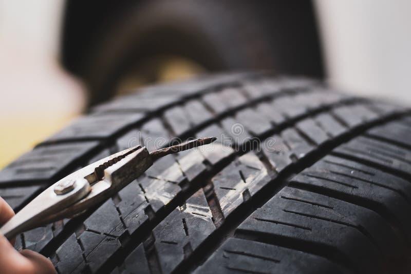 在轮胎的接近的大头钉,轮胎从钉子漏的泄了气的轮胎可能轮胎被修理 图库摄影