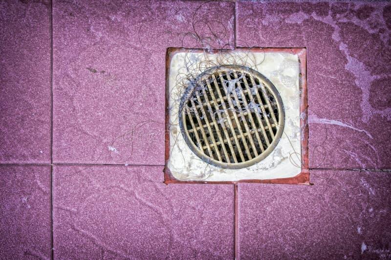 在软泥和泥状物质盖的令人厌恶的污浊的塑料地面排水管 免版税库存图片