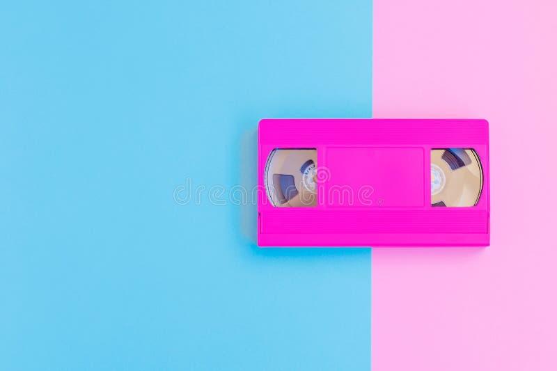 在软的桃红色和蓝纸背景的VHS卡式磁带 最小的概念 创造性的概念 戏院概念 免版税库存图片