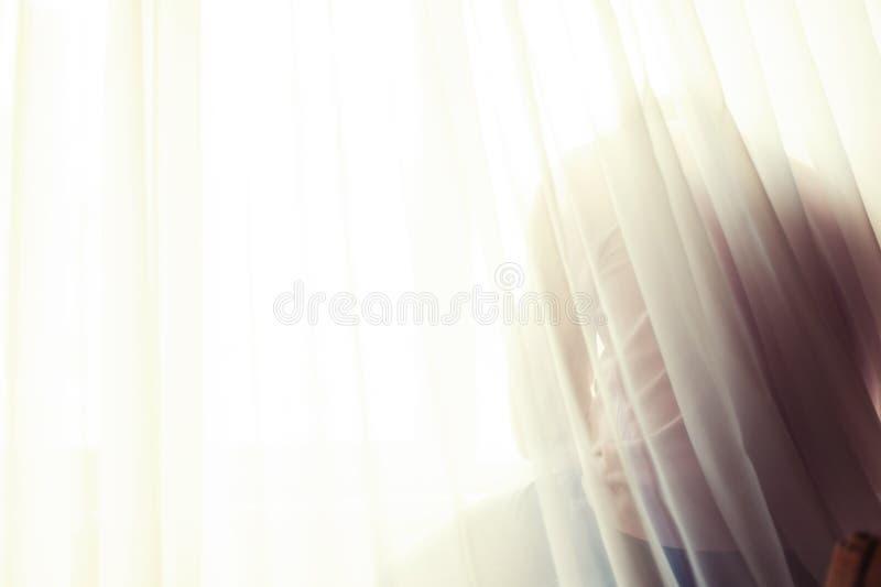 在软的白色帷幕后的Defocused坐的人剪影 免版税图库摄影