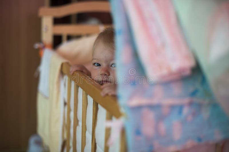 在轻便小床外面的儿童神色 小儿床的孩子 免版税图库摄影