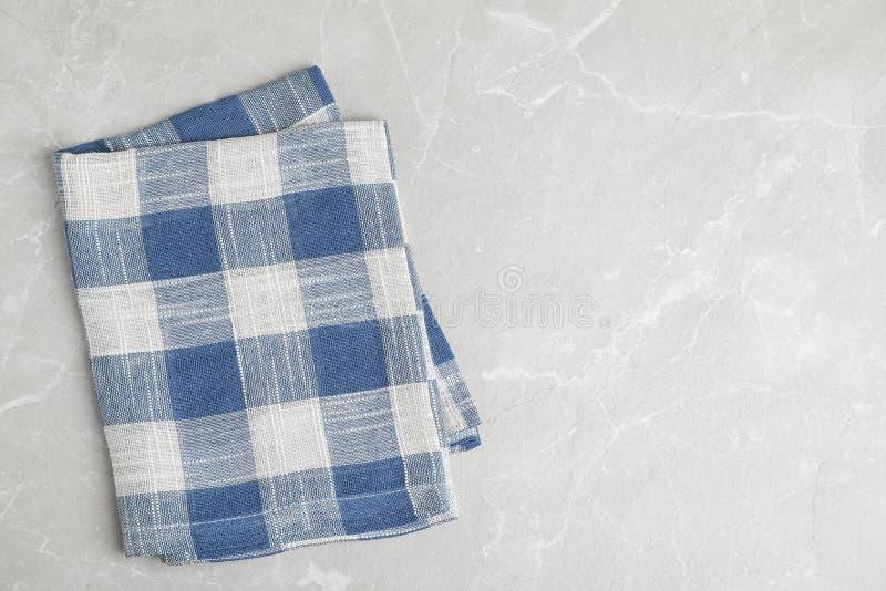 在轻的大理石背景,顶视图的蓝色格子花呢披肩洗碗布 空间为 免版税图库摄影