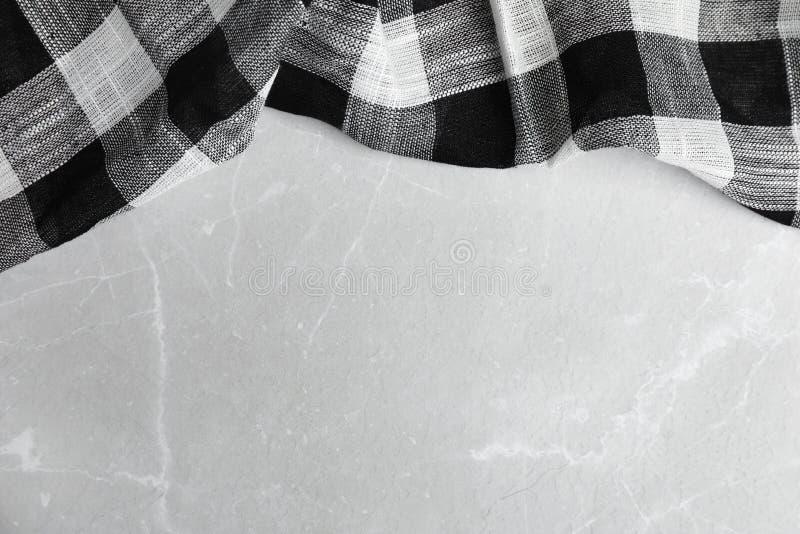 在轻的大理石背景,顶视图的黑格子花呢披肩洗碗布 免版税库存照片