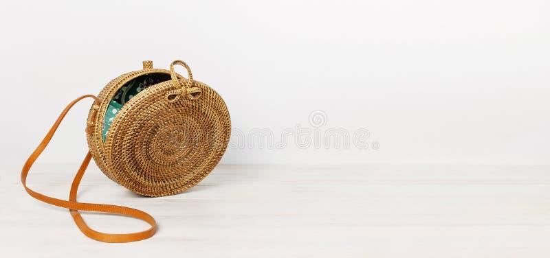 在轻的木背景的时兴的手工制造自然有机藤条袋子 夫人请求做了天然材料 从巴厘岛的Ecobags 免版税库存照片