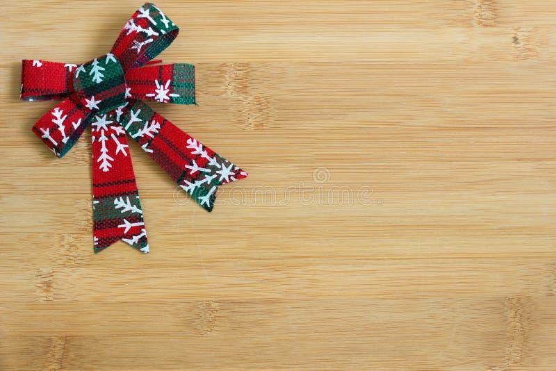 在轻的木背景的红色和白色丝带与圣诞节花圈装饰 免版税库存照片