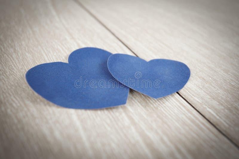 在轻的木背景的蓝纸心脏 库存图片