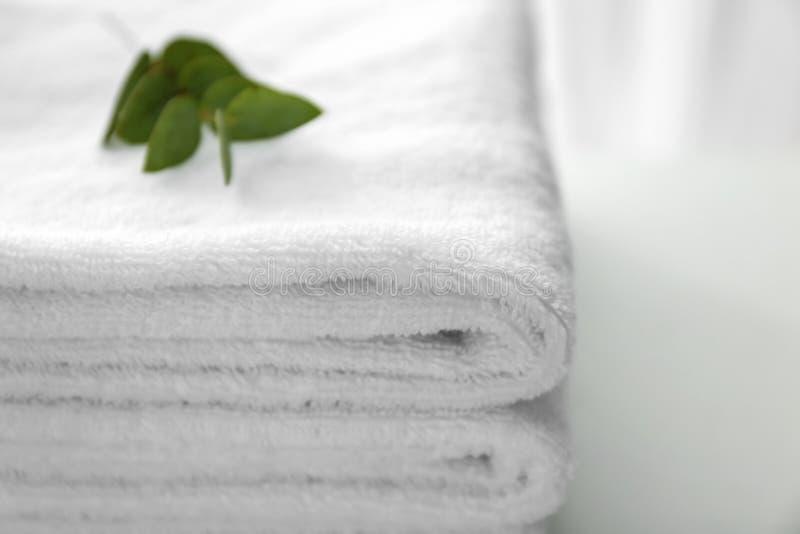 在轻的桌,特写镜头上的被折叠的白色软的毛巾 免版税库存照片