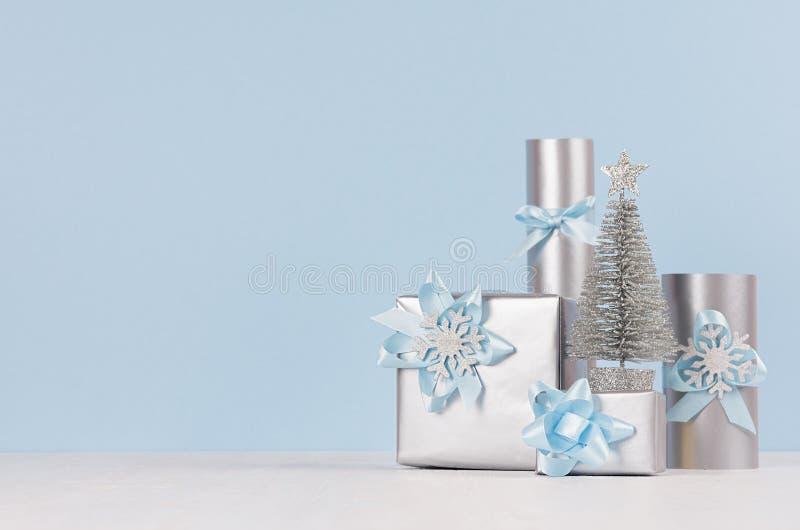 在轻的淡色蓝色和银色颜色-与闪烁和金属礼物盒的装饰杉树的柔和的圣诞节背景 免版税库存图片