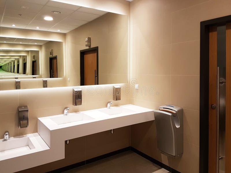 在轻的灰棕色和白色的卫生间内部 圆的陶瓷水盆 镜子、塑料浴皂盒和镀铬物龙头为 免版税库存图片