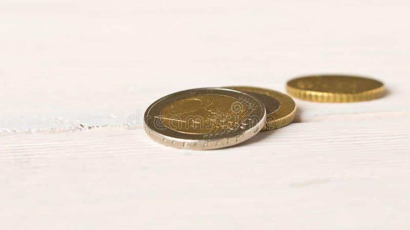 在轻的背景的一些枚欧元硬币 储款的概念 免版税库存图片