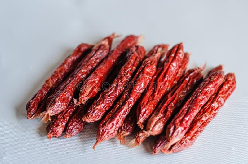 在轻的背景的抽烟的蒜味咸腊肠在轻的背景的风干香肠 r 免版税库存照片