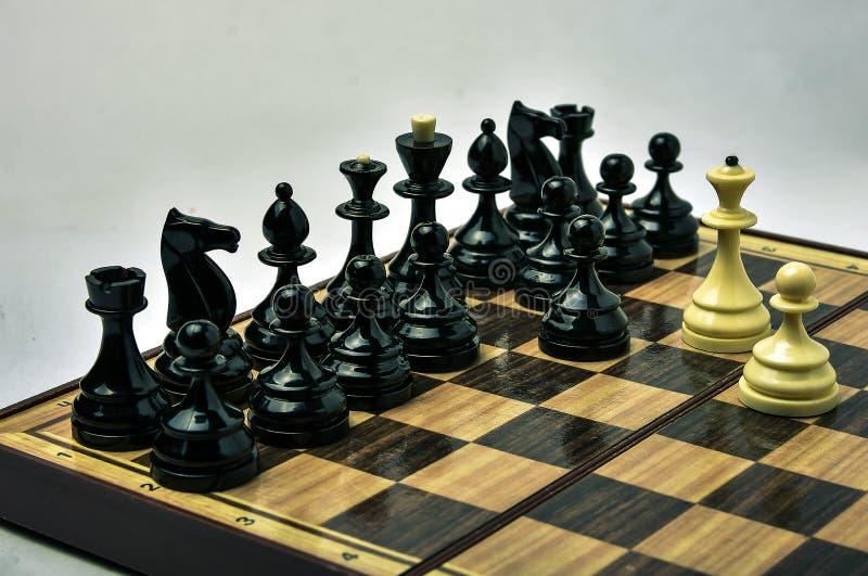 在轻的背景的白色和黑棋子 免版税图库摄影