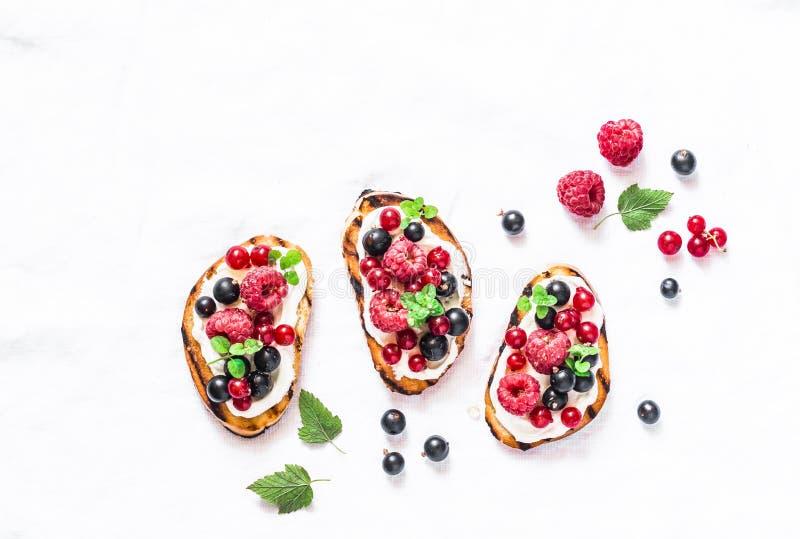 在轻的背景的莓果bruschetta,顶视图 三明治用乳脂干酪,莓,红色和黑醋栗 可口b 免版税库存图片