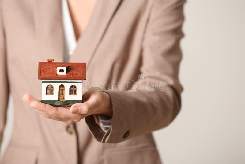 在轻的背景,特写镜头的女性代理藏品房子模型 库存图片