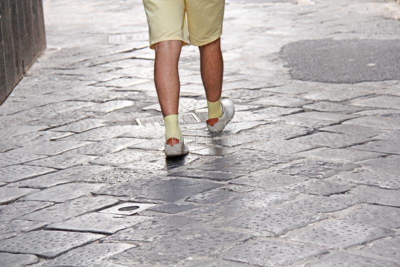 在轻的鞋子和黄色袜子的人的脚沿路前进 西西里岛,意大利的海岛 人的步 库存照片