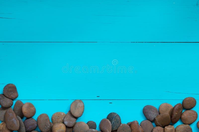 在边的小卵石在织地不很细被绘的蓝色背景 库存照片
