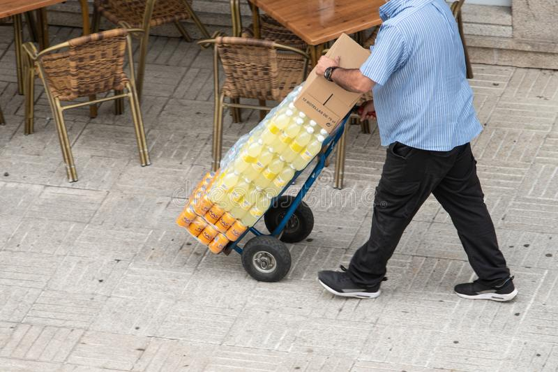 在边路的人运载的饮料在手边推车 工作或运输概念 免版税图库摄影