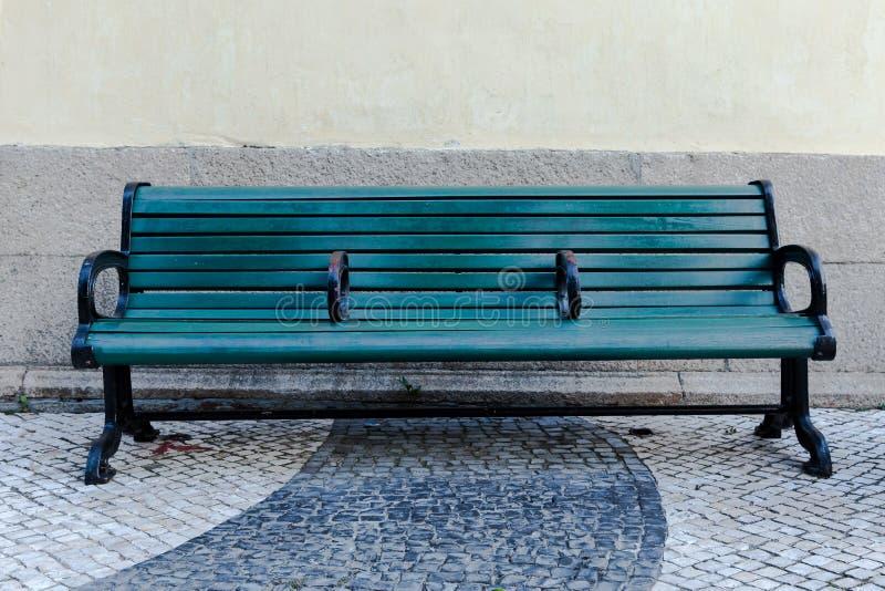 在边路的绿色街道长凳 免版税库存图片