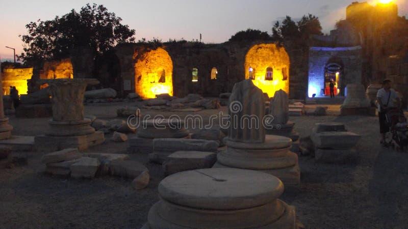 在边,安塔利亚,土耳其的旅游阿波隆寺庙,与特别照明设备的射击,人们是走,坐和采取酸碱度 免版税库存照片