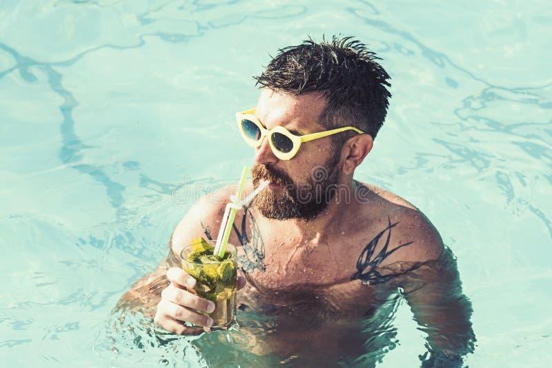 在迈阿密海滩或马尔代夫的暑假 与行家的池边聚会大海的 人游泳和饮料酒客 免版税库存照片